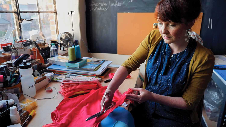 Amanda McCavour in her studio cutting textile