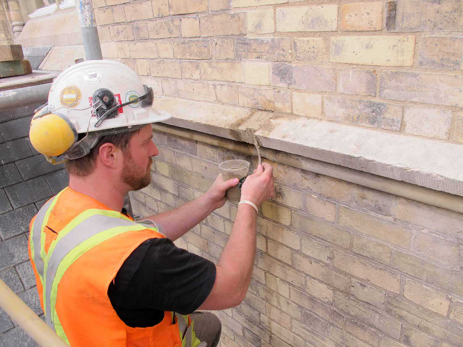 Man carrying out proprietary mortar repair on stone