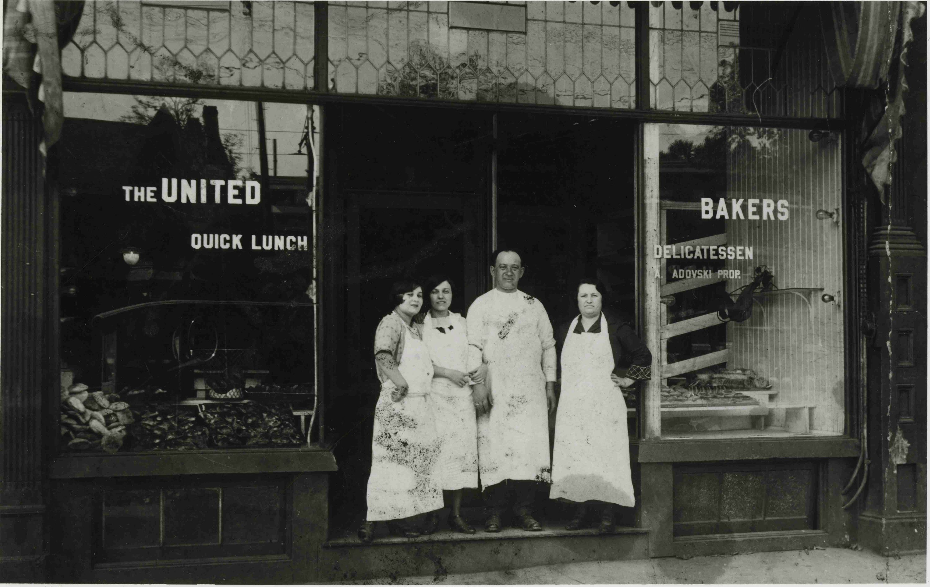 Black and white photo of one man and three woman standing in front of restaurant doorway