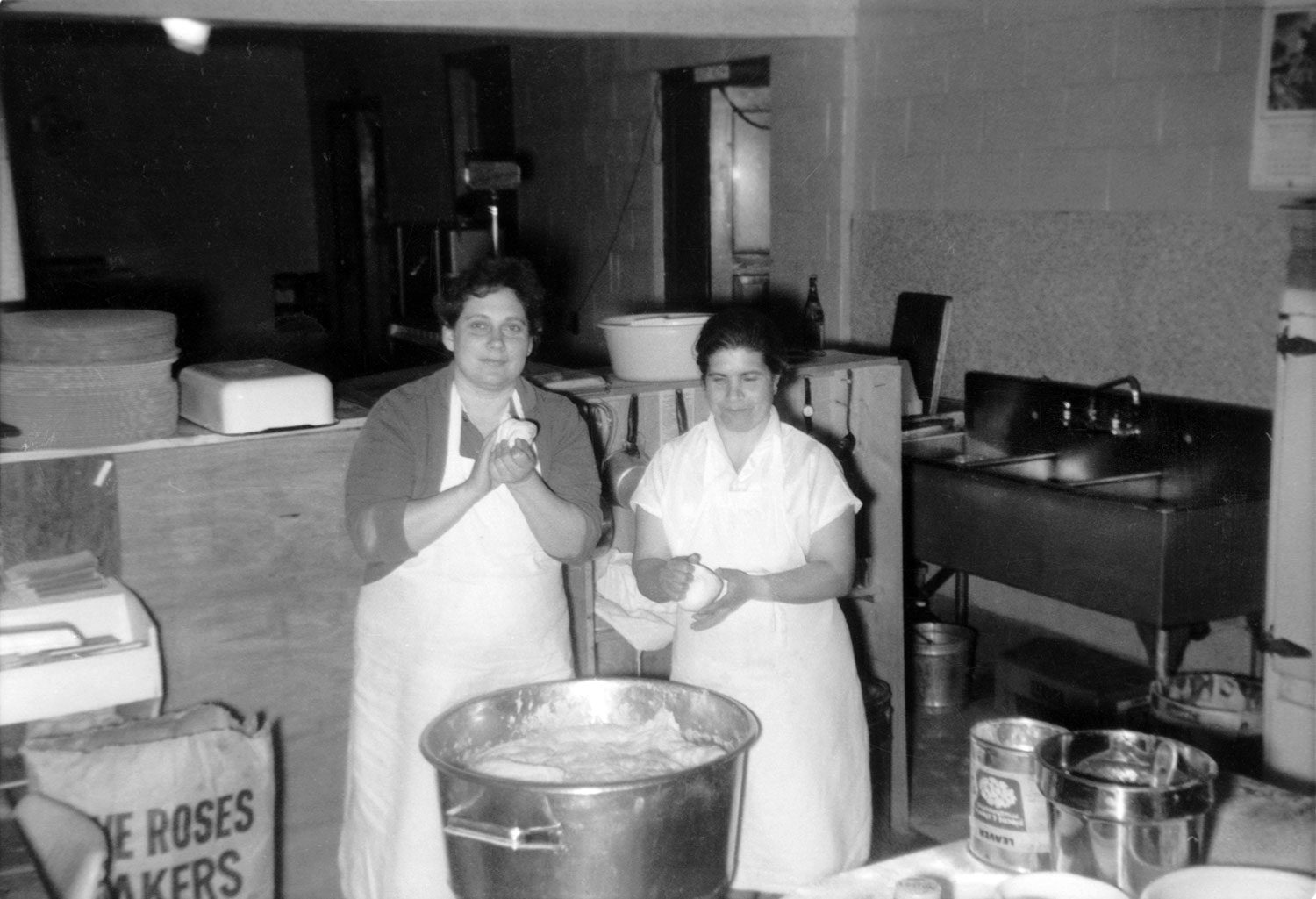 Black and white photo of two women mixing dough