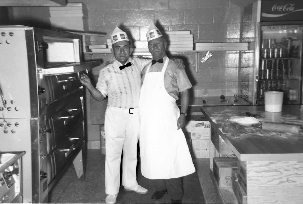 Black and white of two men posing inside restaurant kitchen