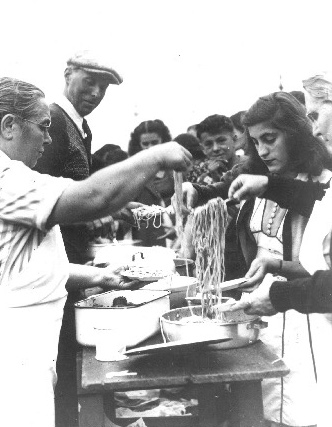 Black and white archival photo of group lining up for food