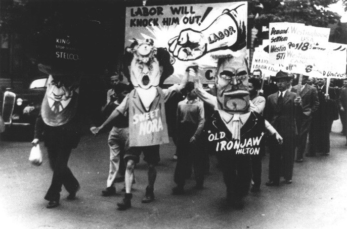 Black and white photo of workers  in costume and holding signs at Labour Day parade.